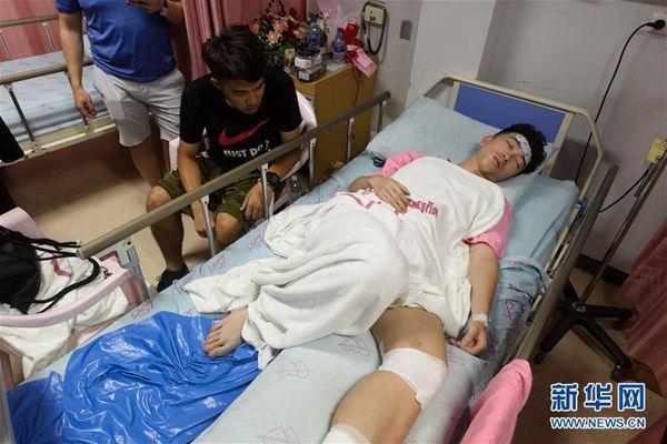 7月7日凌晨,在泰国普吉岛,翻船事故幸存者林宏政(左)在病房照顾受伤