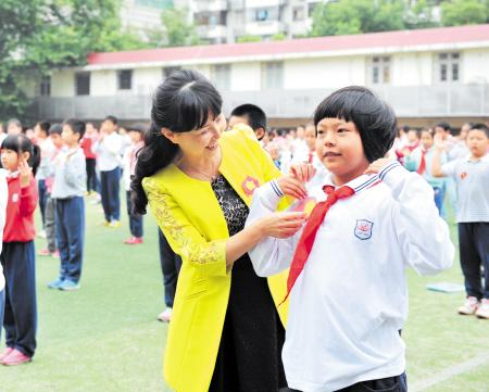 .图为育才小学老师正为学生整理胜利花.   摄-长沙中小学生再次佩