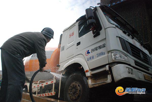 建筑工地工人对进出的施工车辆进行清理